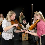 Fiddlers Alina Geslison Bagley and Grace Dayton with Mountain Strings, Folk Dance Ensemble's accompanying band, in 2013. Photo by Mark Philbrick.