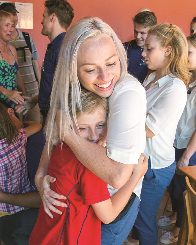 Shelby Tagge, of Contemporary Dance Theatre, hugs a new friend at the Flight's Children's Home in Dobrichovice, Czech Republic.